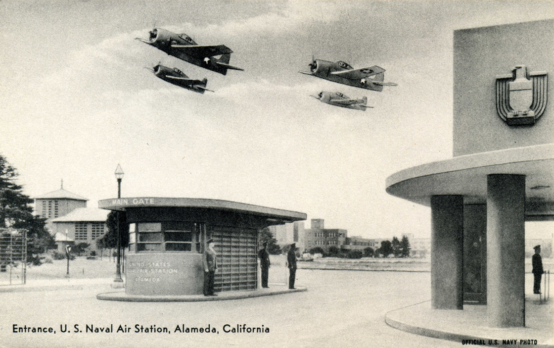 A black and white photgraph of the entrance to the Alameda Naval Air Station featuring several figures at kiosk below four planes flying in formation.